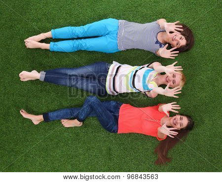 Young women lying on green grass