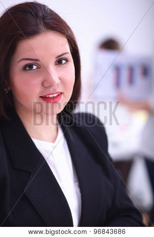 Attractive businesswoman sitting  on desk in the office with cup of coffee