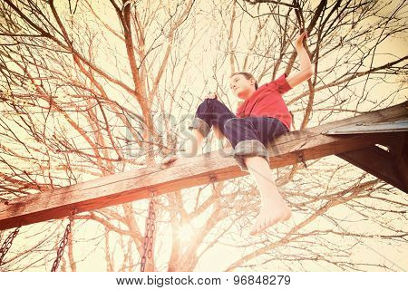 Young boy sitting on the top of a wooden swingset, toned image