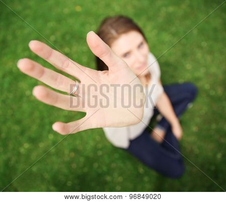 a pretty teen with her palm up toward the camera taken at a wide angle