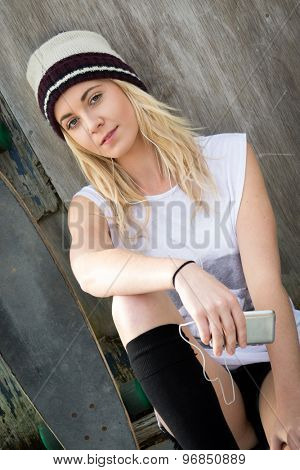 Pretty blond skater girl listening to music
