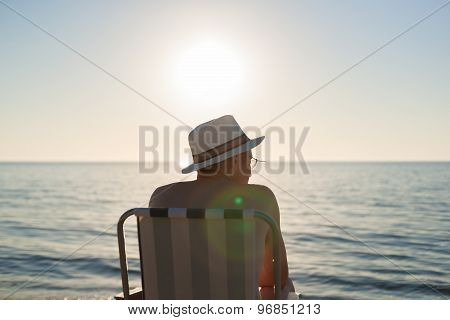 man sitting on chair at sunset beach, backlight, lens flare