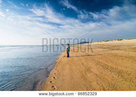 Woman With Camera Standing At Seashore