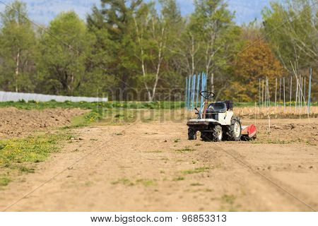 A Mini Tractor In The Land Field