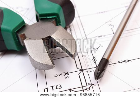Metal Pliers And Screwdriver On Electrical Construction Drawing Of House