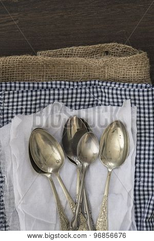 Vintage Cutlery On Cloths On Rustic Wooden Background