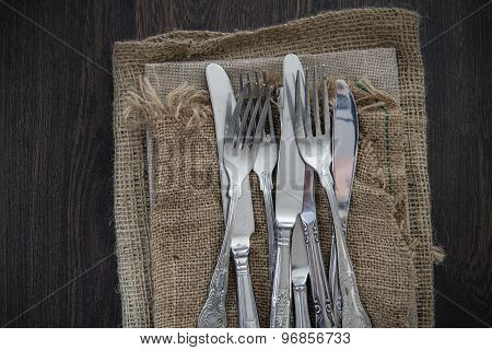 Vintage Cutlery On Hessian Cloths On Rustic Wooden Background
