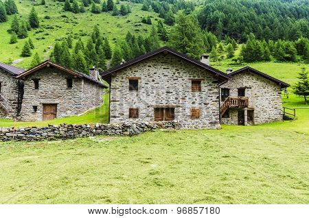 Stone shepherd's house in a peasant village in alpine meadows surrounded by mountains. Northern Ital