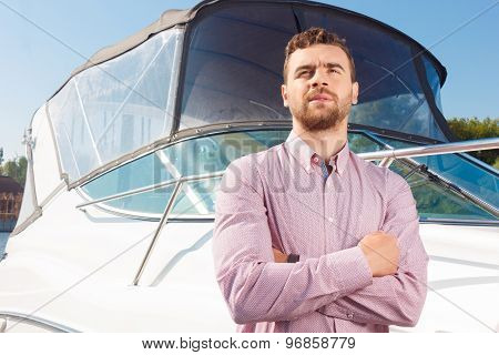 Good looking man standing near yacht