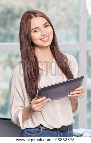 Cheerful business woman holding laptop