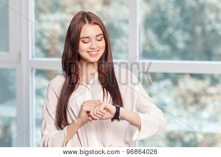 Smiling businesswoman watching time