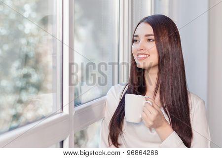 Pleasant woman standing near window