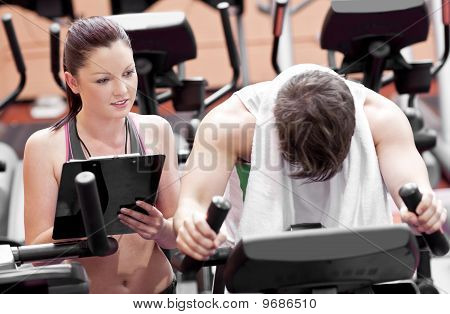 Exhausted Man Doing Exercises While His Coach Is Looking At His Results