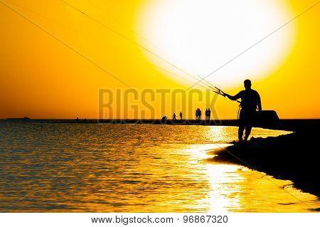 Surfer Silhouette Against Orange Sunset