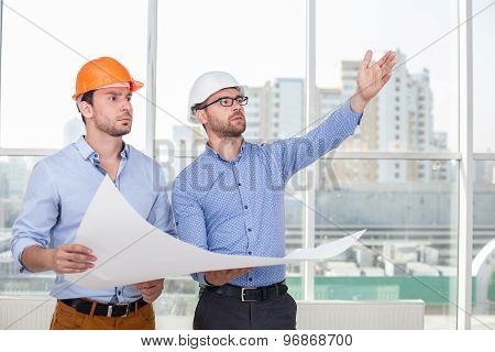 Attractive young architect is explaining a building construction