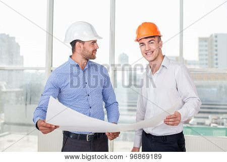 Attractive young engineer is explaining the plan of building