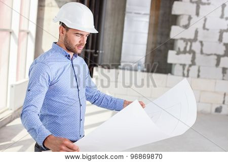 Attractive young builder is checking the layout of building