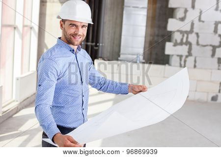 Handsome young engineer is analyzing the plan of a project