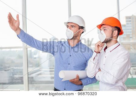 Cheerful young builders are discussing the plan of building