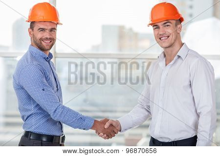 Attractive young workers is congratulating each other