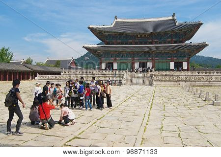 Tourists make group travel photo in front of the Gyeongbokgung Palace in Seoul, Korea.
