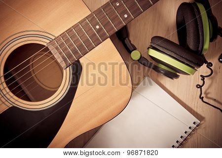 Notebook And Headphone On Wooden Background With Guitar