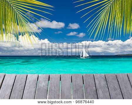Wooden Pier With View On Sailboat In The Sea