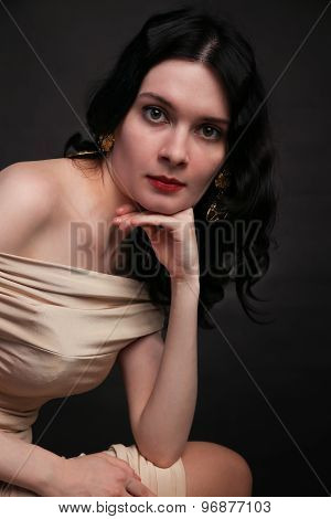Portrait of beautiful young woman sitting over black background