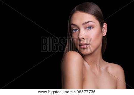 close portrait of a beautiful girl with a natural make-up nude. Isolated on black background. Copy s