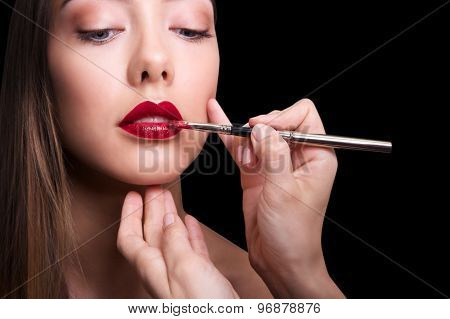 close portrait of beautiful girl making make up. Isolated on black background. Copy space.