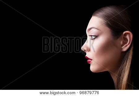 Close portrait of a beautiful girl with a red lips and smoky eyes. Isolated on black background. Cop