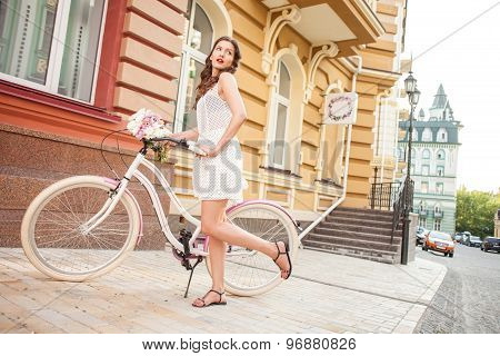 Cheerful young girl is cycling in city