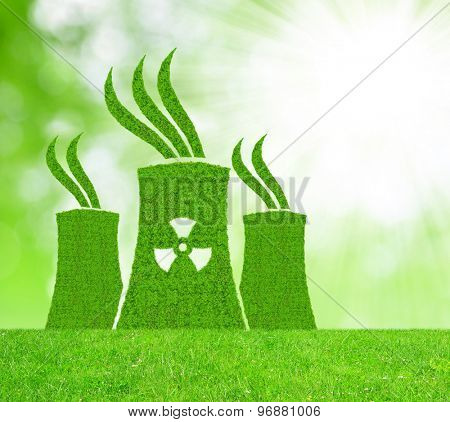 Green nuclear power plant icon on meadow