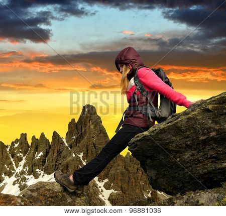 Girl sitting on rock, in the background Paternkofel at sunset ,Dolomite Alps, Italy