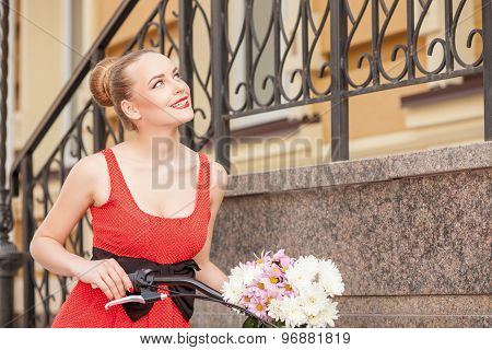 Cute young woman is cycling across city