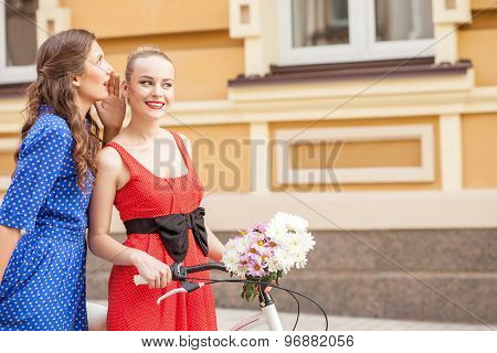 Cheerful young female friends are walking in town