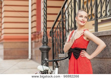 Beautiful young woman is cycling in city