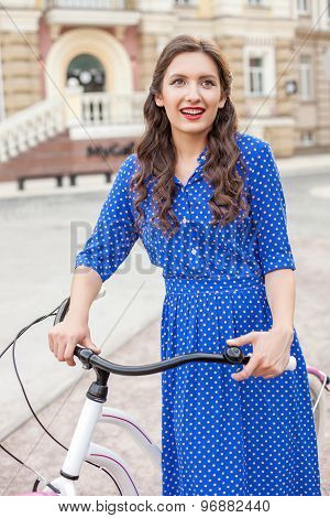 Attractive young woman is cycling across street