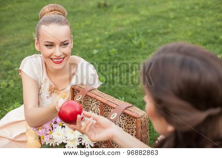 Pretty young girls are making picnic in park