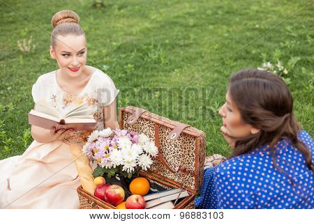 Pretty young women are resting on picnic