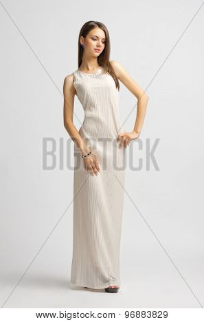 Young girl in long dress on grey background