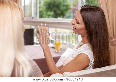 Cheerful young woman is sharing her news with friend