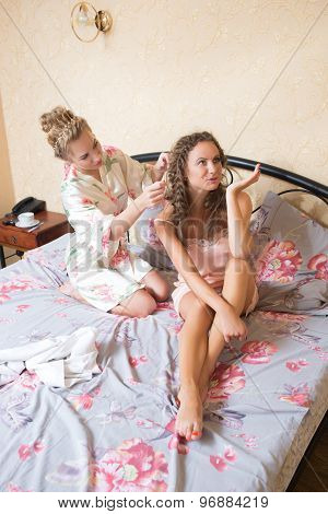 girl friends blond attractive young women sitting in bed in pajamas one doing other braid pigtail