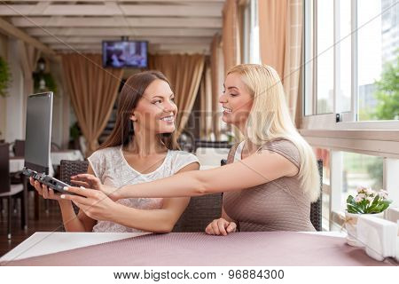 Beautiful young girls are using notebook in cafeteria