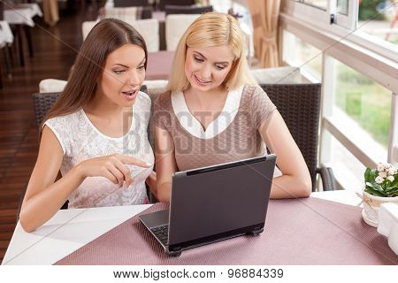 Cheerful young woman are using a laptop in cafe