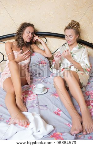 friendship - two smiling girls have Gossip,white bed