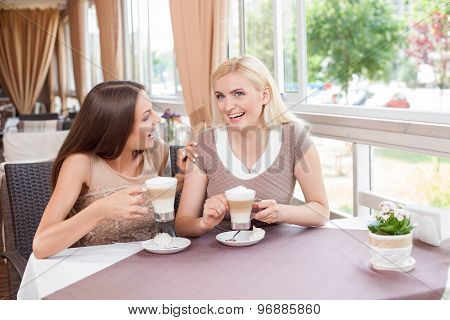 Beautiful young women are spending time in cafe