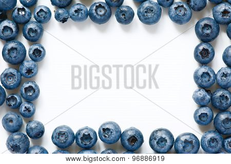 Frame from fresh blueberries laid around on the white background