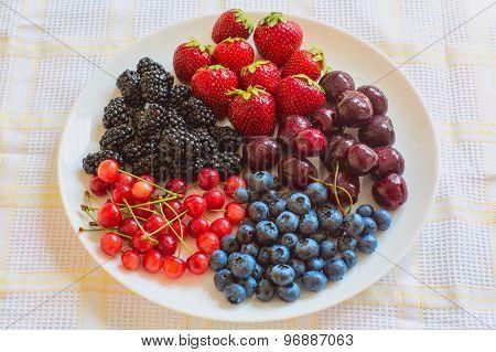 Plate with fresh fruits: cherries, berries, blackberries, blueberries, strawberries