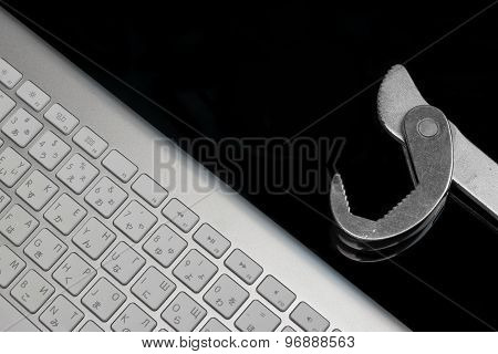 Chrome Plated Wrench And Wireless Keyboard Isolated On Black